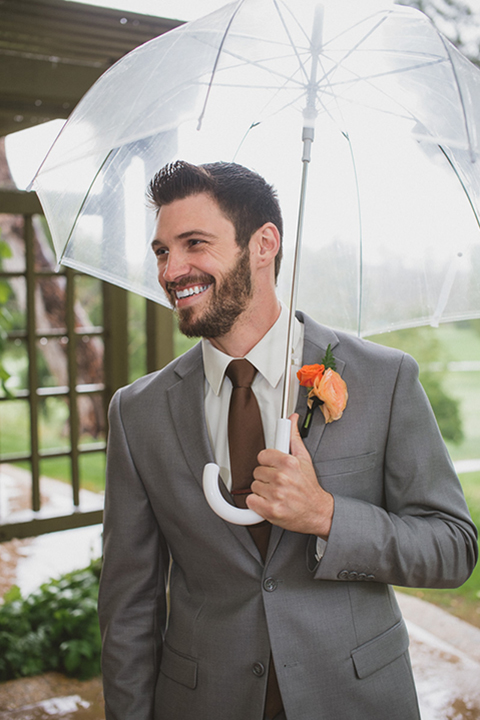 Temecula outdoor wedding at temecula creek inn groom grey notch lapel suit with a white dress shirt and long brown tie with yellow and orange floral boutonniere holding clear umbrella