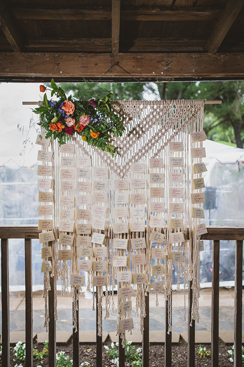 Temecula outdoor wedding at temecula creek inn table set up light brown wood table with matching wood chairs and colorful flower centerpiece decor with colorful glassware and white place settings with brown wood table numbers with white calligraphy writing