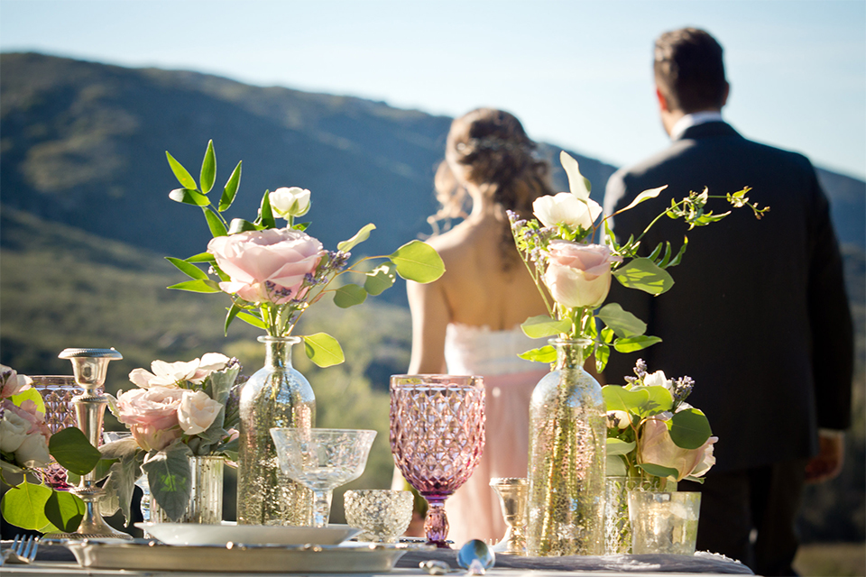 San diego outdoor woodland wedding shoot table set up white wood table with vintage decor and blush pink glassware with white and green flower centerpiece decor with white vintage benches and white place settings with bride and groom holding hands