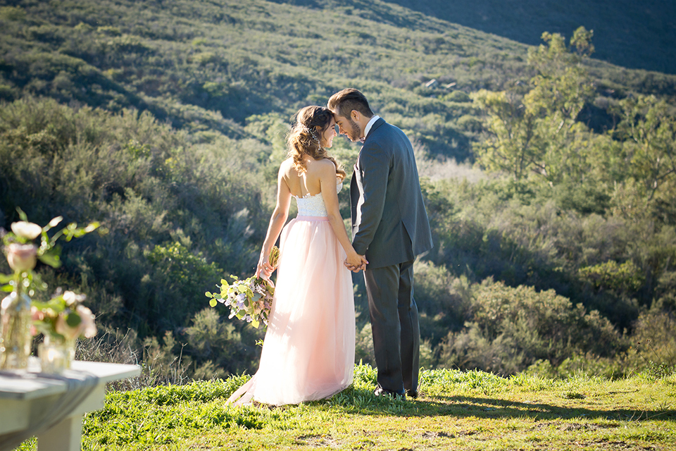 San diego outdoor woodland wedding shoot bride blush pink chiffon strapless gown with a sweetheart neckline and groom navy blue shawl lapel tuxedo with a matching vest and white dress shirt with a long pink striped tie and white floral boutonniere holding hands and kissing