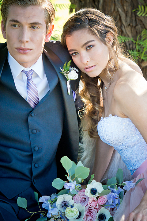 San diego outdoor woodland wedding shoot bride blush pink chiffon strapless gown with a sweetheart neckline and groom navy blue shawl lapel tuxedo with a matching vest and white dress shirt with a long pink striped tie and white floral boutonniere sitting and hugging close up