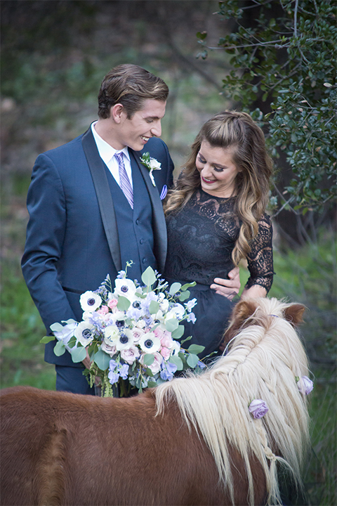 San diego outdoor woodland wedding shoot bride black chiffon gown with long lace sleeves and high lace neckline holding white floral bridal bouquet with groom navy blue shawl lapel tuxedo with matching vest and white dress shirt with a long pink striped tie and white floral boutonniere standing next to pony wedding photo idea