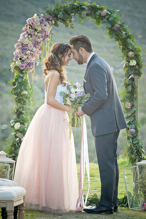 San diego outdoor woodland wedding shoot bride blush pink chiffon strapless gown with a sweetheart neckline and groom navy blue shawl lapel tuxedo with a matching vest and white dress shirt with a long pink striped tie and white floral boutonniere holding hands during ceremony and bride holding white floral bridal bouquet