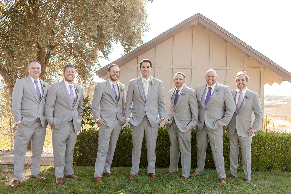 Temecula outddor wedding at callaway winery groom heather grey suit with matching vest and white dress shirt with long ivory tie and purple floral boutonniere holding jacket with groomsmen heather grey suits with matching vests and long purple ties