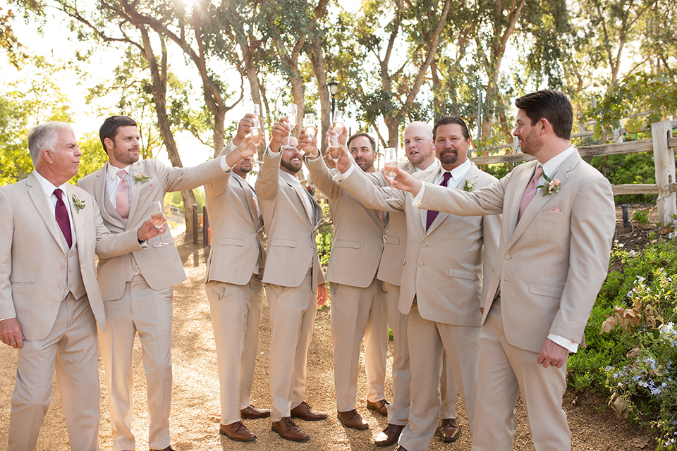 Temecula outdoor rustic wedding at lake oak meadows groom tan notch lapel suit with matching vest and white dress shirt and long white tie with red floral boutonniere standing with groomsmen tan suits with drinks