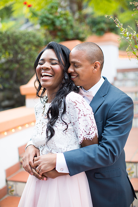 Rancho las lomas outdoor engagement shoot bride light pink tulle skirt with a white lace short sleeve top with groom slate blue notch lapel suit with a white dress shirt and blush pink bow tie with a pink floral boutonniere hugging and laughing