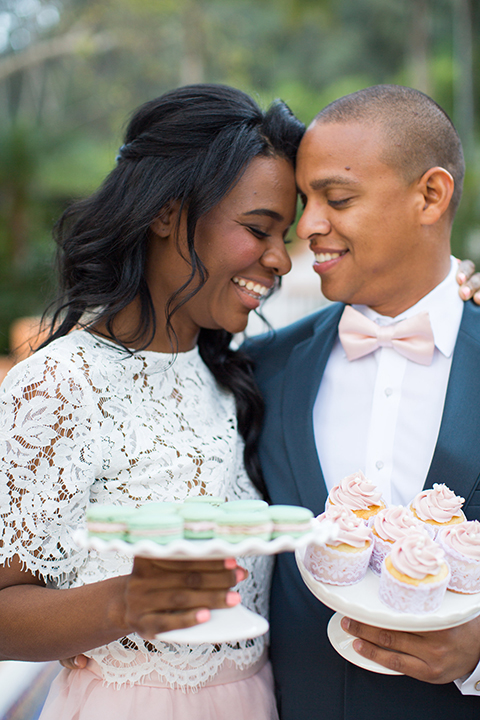Rancho las lomas outdoor engagement shoot bride light pink tulle skirt with a white lace short sleeve top with groom slate blue notch lapel suit with a white dress shirt and blush pink bow tie with a pink floral boutonniere hugging close up and holding desserts