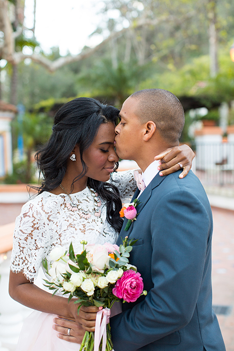 Rancho las lomas outdoor engagement shoot bride light pink tulle skirt with a white lace short sleeve top with groom slate blue notch lapel suit with a white dress shirt and blush pink bow tie with a pink floral boutonniere hugging close up and bride holding white and pink floral bridal bouquet