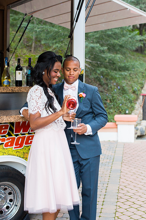 Rancho las lomas outdoor engagement shoot bride light pink tulle skirt with a white lace short sleeve top with groom slate blue notch lapel suit with a white dress shirt and blush pink bow tie with a pink floral boutonniere standing and hugging holding drinks