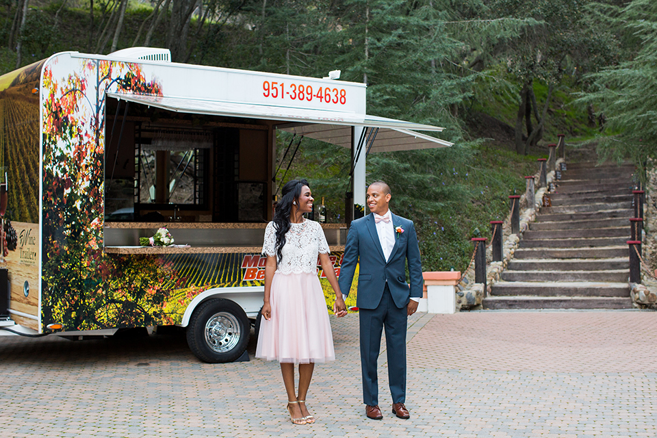 Rancho las lomas outdoor engagement shoot bride light pink tulle skirt with a white lace short sleeve top with groom slate blue notch lapel suit with a white dress shirt and blush pink bow tie with a pink floral boutonniere standing by food truck holding hands