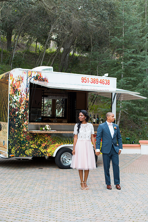 Rancho las lomas outdoor engagement shoot bride light pink tulle skirt with a white lace short sleeve top with groom slate blue notch lapel suit with a white dress shirt and blush pink bow tie with a pink floral boutonniere standing by food truck holding hands and looking away walking