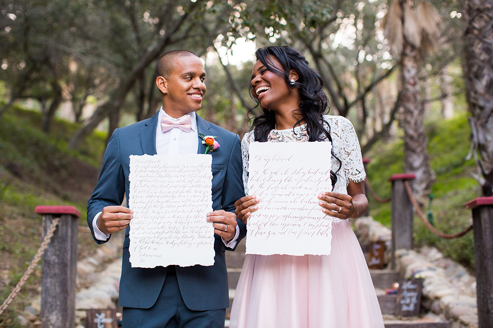 Rancho las lomas outdoor engagement shoot bride light pink tulle skirt with a white lace short sleeve top with groom slate blue notch lapel suit with a white dress shirt and blush pink bow tie with a pink floral boutonniere standing and holding vows during ceremony