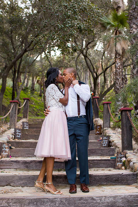 Rancho las lomas outdoor engagement shoot bride light pink tulle skirt with a white lace short sleeve top with groom slate blue notch lapel suit with a white dress shirt and blush pink bow tie with a pink floral boutonniere standing on stairs and kissing and hugging during ceremony