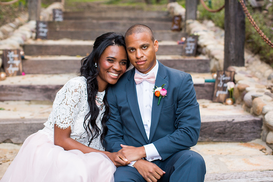 Rancho las lomas outdoor engagement shoot bride light pink tulle skirt with a white lace short sleeve top with groom slate blue notch lapel suit with a white dress shirt and blush pink bow tie with a pink floral boutonniere sitting on stairs after ceremony hugging