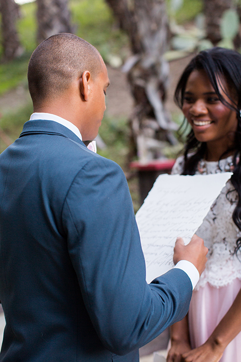 Rancho las lomas outdoor engagement shoot bride light pink tulle skirt with a white lace short sleeve top with groom slate blue notch lapel suit with a white dress shirt and blush pink bow tie with a pink floral boutonniere standing during ceremony groom reading vows