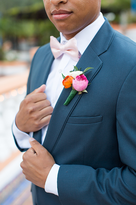 Rancho las lomas outdoor engagement shoot groom slate blue notch lapel suit with a white dress shirt and blush pink bow tie with a pink floral boutonniere close up