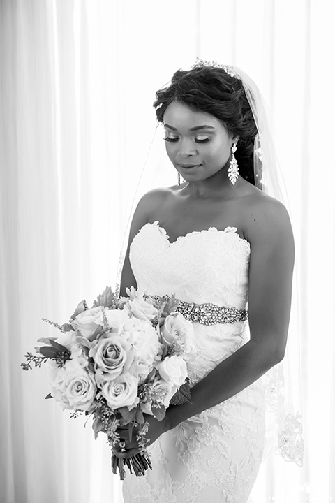 San diego outdoor wedding at ultimate skybox bride form fitting strapless lace gown with a sweetheart neckline and crystal belt with long veil holding white floral bridal bouquet black and white