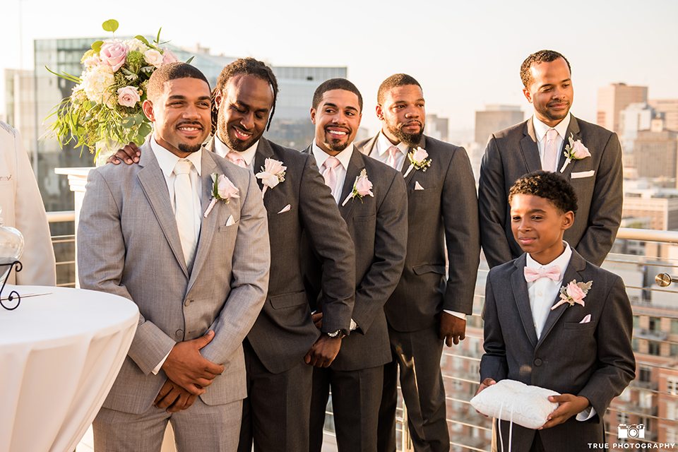 San diego outdoor wedding at ultimate skybox groom heather grey notch lapel suit with a white dress shirt and matching vest with a long white tie and white pocket square with a white floral boutonniere standing with groomsmen during ceremony charcoal grey suits with long white ties and white floral boutonnieres