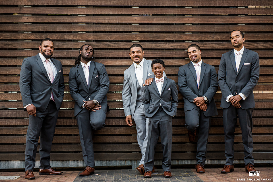 San diego outdoor wedding at ultimate skybox groom heather grey notch lapel suit with a white dress shirt and matching vest with a long white tie and white pocket square with a white floral boutonniere with groomsmen charcoal grey suits with long white ties standing