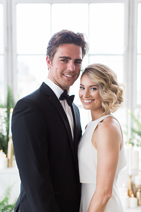 Downtown los angeles wedding shoot at fd photo studio bride form fitting simple gown with a high halter neckline and groom black notch lapel tuxedo by michael kors with a white dress shirt and black bow tie smiling and holding hands