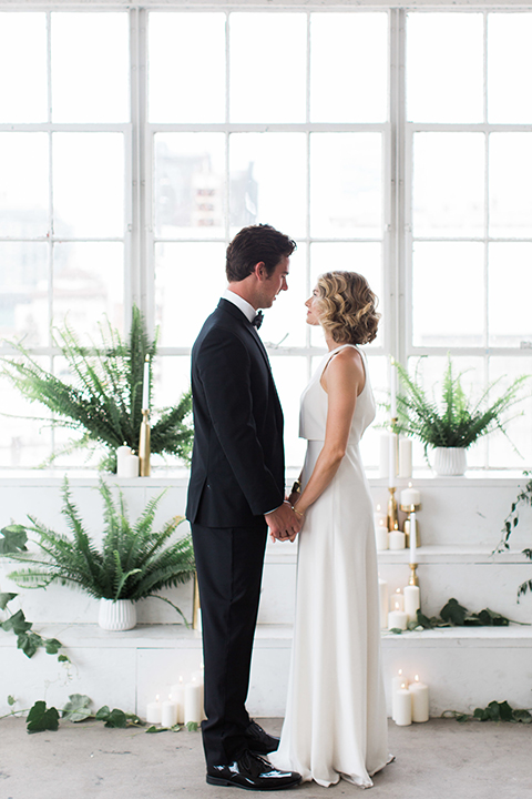 Downtown los angeles wedding shoot at fd photo studio bride form fitting simple gown with a high halter neckline and groom black notch lapel tuxedo by michael kors with a white dress shirt and black bow tie holding hands with greenery decor
