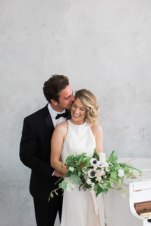 Downtown los angeles wedding shoot at fd photo studio bride form fitting simple gown with a high halter neckline and groom black notch lapel tuxedo by michael kors with a white dress shirt and black bow tie hugging and smiling bride holding white and green floral bridal bouquet