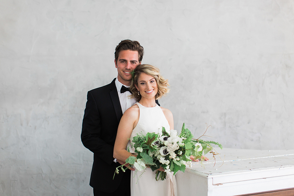 Downtown los angeles wedding shoot at fd photo studio bride form fitting simple gown with a high halter neckline and groom black notch lapel tuxedo by michael kors with a white dress shirt and black bow tie hugging and bride holding white and green floral bridal bouquet