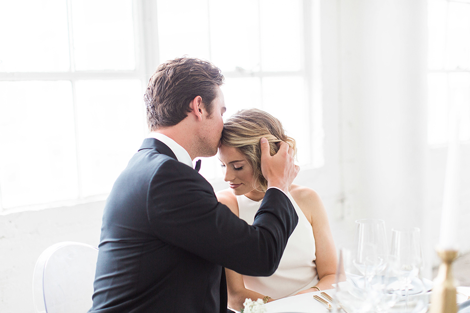 Downtown los angeles wedding shoot at fd photo studio bride form fitting simple gown with a high halter neckline and groom black notch lapel tuxedo by michael kors with a white dress shirt and black bow tie sitting at table and kissing close up
