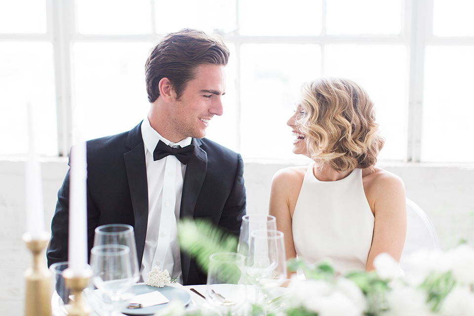 Downtown los angeles wedding shoot at fd photo studio bride form fitting simple gown with a high halter neckline and groom black notch lapel tuxedo by michael kors with a white dress shirt and black bow tie sitting at table smiling and laughing close up