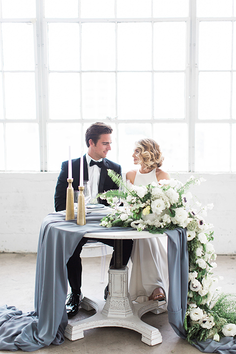 Downtown los angeles wedding shoot at fd photo studio bride form fitting simple gown with a high halter neckline and groom black notch lapel tuxedo by michael kors with a white dress shirt and black bow tie sitting at table smiling