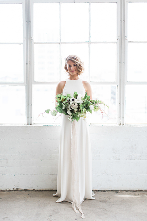 Downtown los angeles wedding shoot at fd photo studio bride form fitting simple gown with a high halter neckline holding white and green floral bridal bouquet