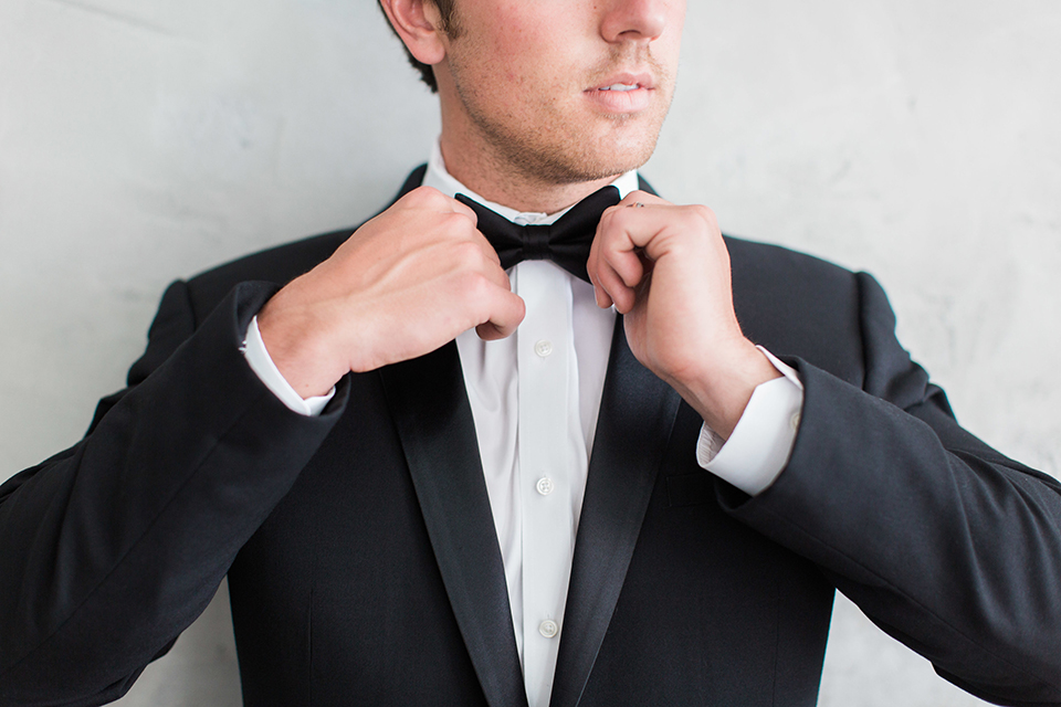Downtown los angeles wedding shoot at fd photo studio groom black notch lapel tuxedo by michael kors with a white dress shirt and black bow tie fixing tie close up