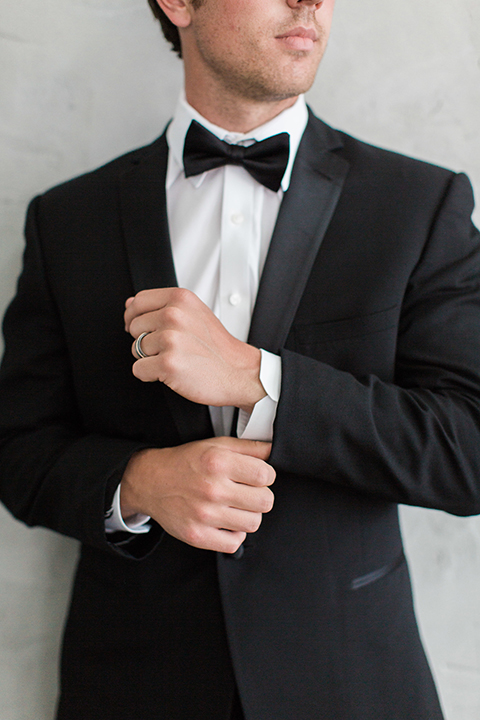 Downtown los angeles wedding shoot at fd photo studio groom black notch lapel tuxedo by michael kors with a white dress shirt and black bow tie holding sleeve