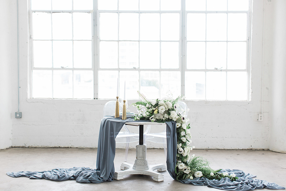 Downtown los angeles wedding shoot at fd photo studio table set up with grey table linen and white and green flower decor with clear ghost chairs and white and grey place settings with white candle decor and piano