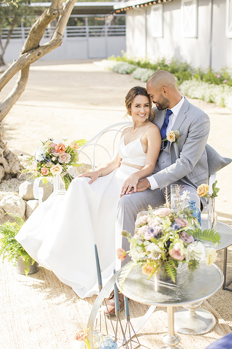 Los angeles outdoor wedding at brookview ranch bride two piece wedding dress with tulle skirt and crop top bodice with thin straps and a sweetheart neckline and groom heather grey notch lapel suit with a matching vest and white dress shirt with a long navy blue tie and white floral boutonniere sitting on white couch with white and pink flower decor