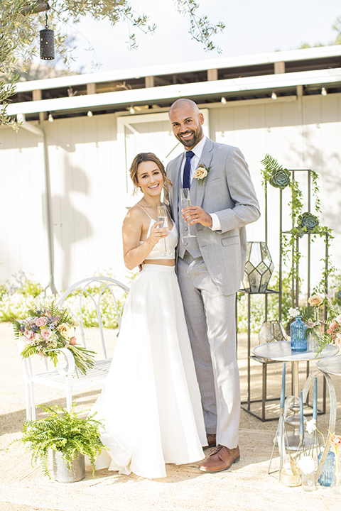 Los angeles outdoor wedding at brookview ranch bride two piece wedding dress with tulle skirt and crop top bodice with thin straps and a sweetheart neckline and groom heather grey notch lapel suit with a matching vest and white dress shirt with a long navy blue tie and white floral boutonniere standing and holding drinks by wedding table and decor