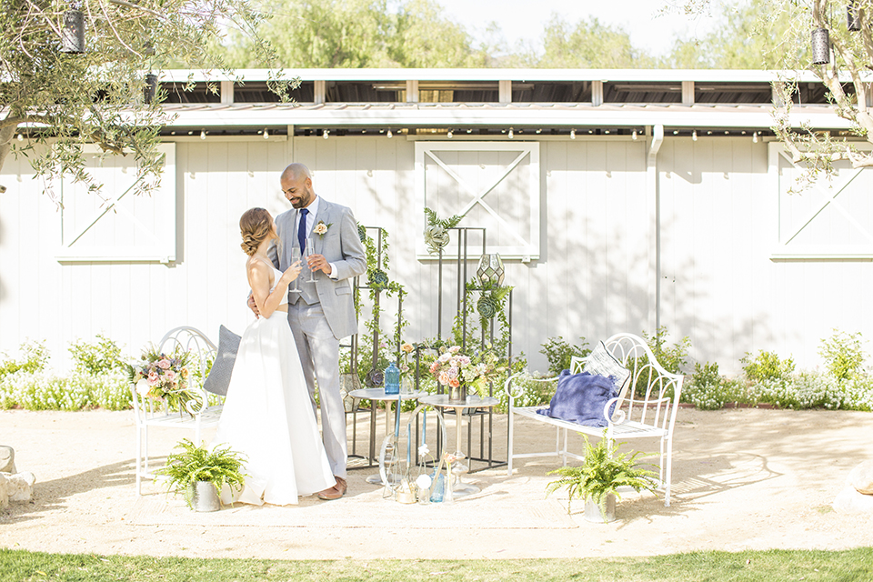 Los angeles outdoor wedding at brookview ranch bride two piece wedding dress with tulle skirt and crop top bodice with thin straps and a sweetheart neckline and groom heather grey notch lapel suit with a matching vest and white dress shirt with a long navy blue tie and white floral boutonniere standing and hugging by white couch and table wedding flower decor