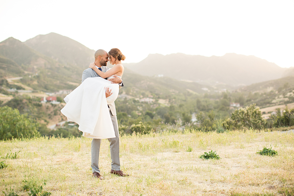 Los angeles outdoor wedding at brookview ranch bride two piece wedding dress with tulle skirt and crop top bodice with thin straps and a sweetheart neckline and groom heather grey notch lapel suit with a matching vest and white dress shirt with a long navy blue tie and white floral boutonniere hugging and carrying bride