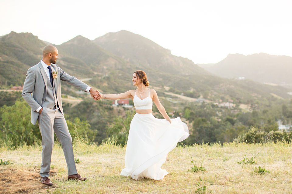 Los angeles outdoor wedding at brookview ranch bride two piece wedding dress with tulle skirt and crop top bodice with thin straps and a sweetheart neckline and groom heather grey notch lapel suit with a matching vest and white dress shirt with a long navy blue tie and white floral boutonniere standing and holding hands