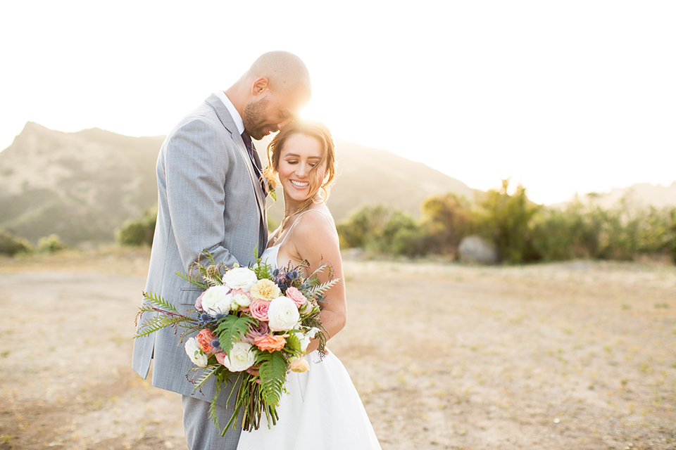 Los angeles outdoor wedding at brookview ranch bride two piece wedding dress with tulle skirt and crop top bodice with thin straps and a sweetheart neckline and groom heather grey notch lapel suit with a matching vest and white dress shirt with a long navy blue tie and white floral boutonniere hugging and bride holding white and pink floral bridal bouquet