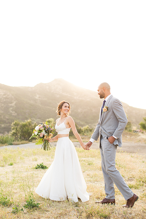 Los angeles outdoor wedding at brookview ranch bride two piece wedding dress with tulle skirt and crop top bodice with thin straps and a sweetheart neckline and groom heather grey notch lapel suit with a matching vest and white dress shirt with a long navy blue tie and white floral boutonniere holding hands and bride holding white and pink floral bridal bouquet