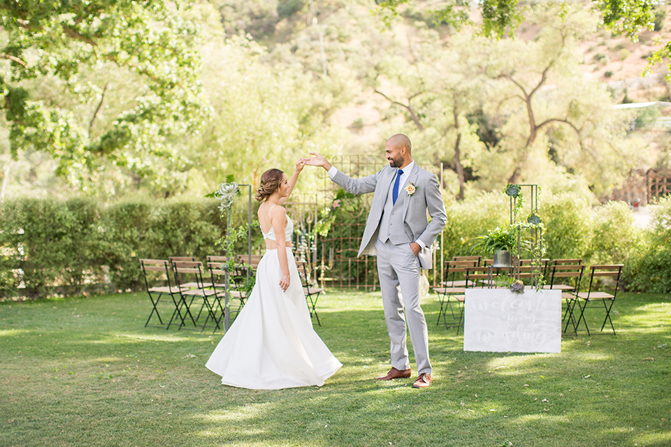 Los angeles outdoor wedding at brookview ranch bride two piece wedding dress with tulle skirt and crop top bodice with thin straps and a sweetheart neckline and groom heather grey notch lapel suit with a matching vest and white dress shirt with a long navy blue tie and white floral boutonniere holding hands and dancing after ceremony