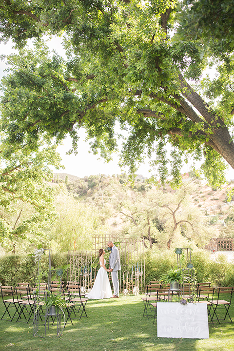 Los angeles outdoor wedding at brookview ranch bride two piece wedding dress with tulle skirt and crop top bodice with thin straps and a sweetheart neckline and groom heather grey notch lapel suit with a matching vest and white dress shirt with a long navy blue tie and white floral boutonniere holding hands during ceremony with backdrop and flower decor