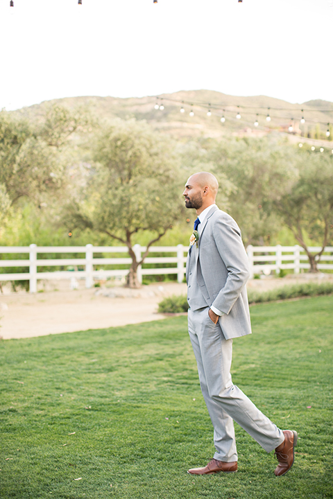 Los angeles outdoor wedding at brookview ranch groom heather grey notch lapel suit with a matching vest and white dress shirt and long blue tie and white floral boutonniere standing