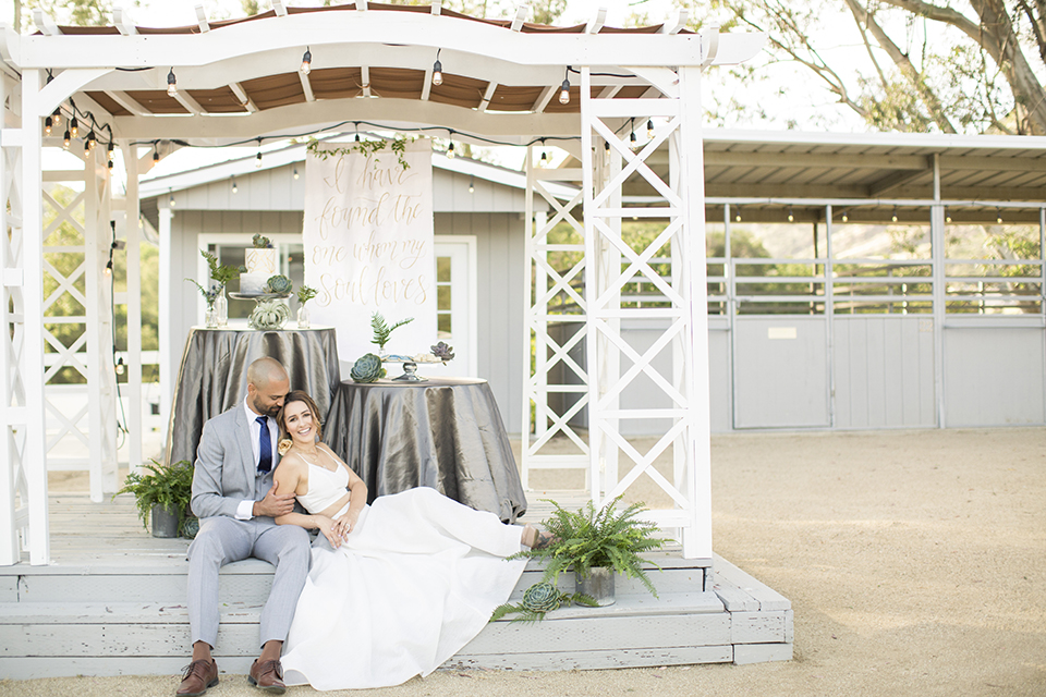 Los angeles outdoor wedding at brookview ranch bride two piece wedding dress with tulle skirt and crop top bodice with thin straps and a sweetheart neckline and groom heather grey notch lapel suit with a matching vest and white dress shirt with a long navy blue tie and white floral boutonniere sitting on ground by table with flower decor