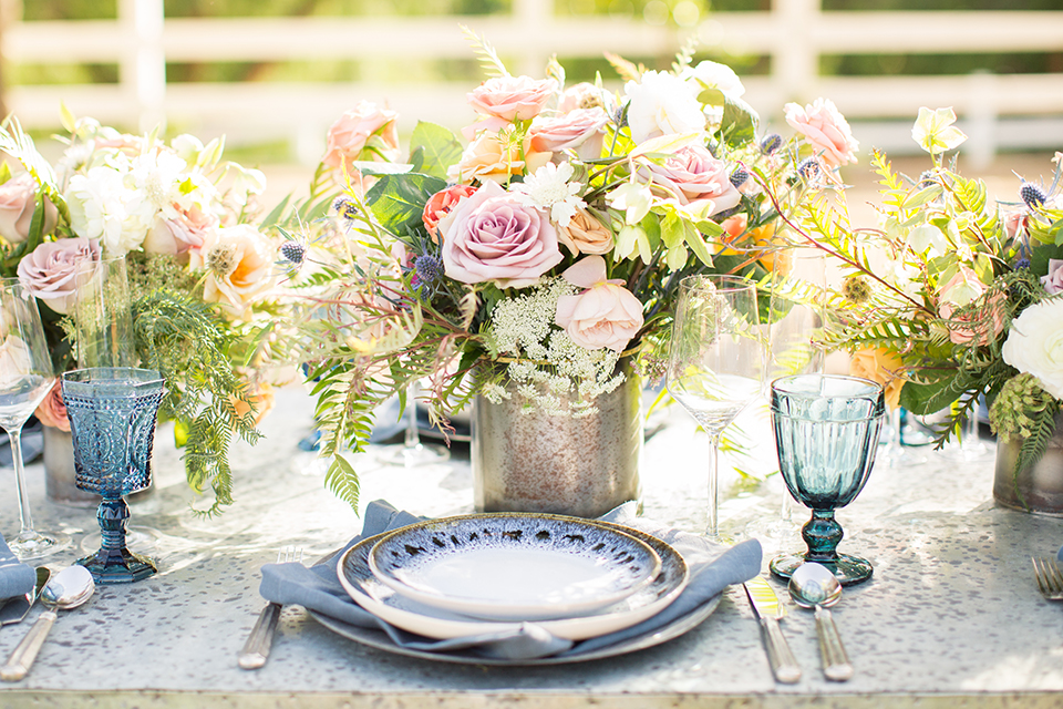 Los angeles outdoor wedding at brookview ranch table set up dark brown wood table with matching wood chairs with blue place settings and blue glasses with white and pink flower decor with gold vases and greenery decor