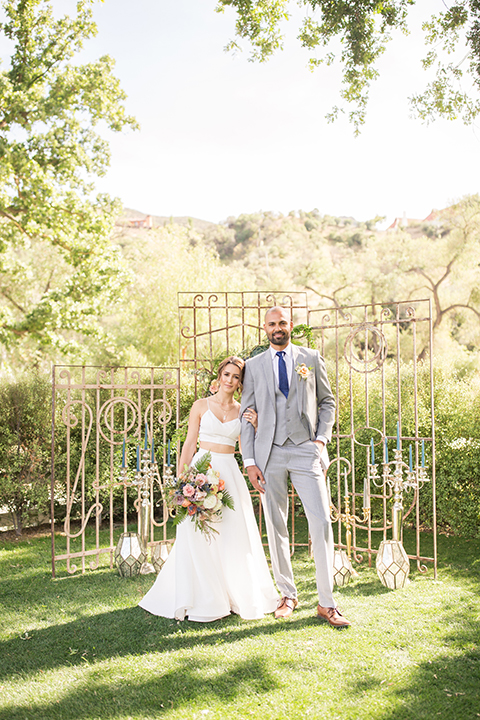 Los angeles outdoor wedding at brookview ranch bride two piece wedding dress with tulle skirt and crop top bodice with thin straps and a sweetheart neckline and groom heather grey notch lapel suit with a matching vest and white dress shirt with a long navy blue tie and white floral boutonniere hugging and holding hands during ceremony with backdrop and flower decor