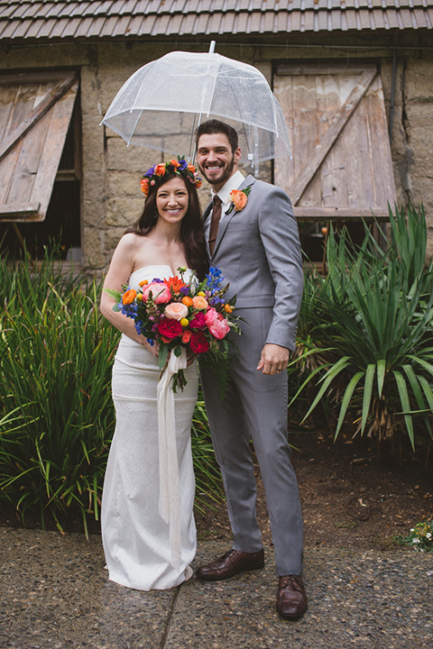 Temecula outdoor wedding at temecula creek inn bride form fitting simple strapless gown with a straight neckline and teal rain boots with groom grey notch lapel suit with a white dress shirt and long brown tie with an orange floral boutonniere standing holding clear umbrella and bride holding colorful floral bridal bouquet
