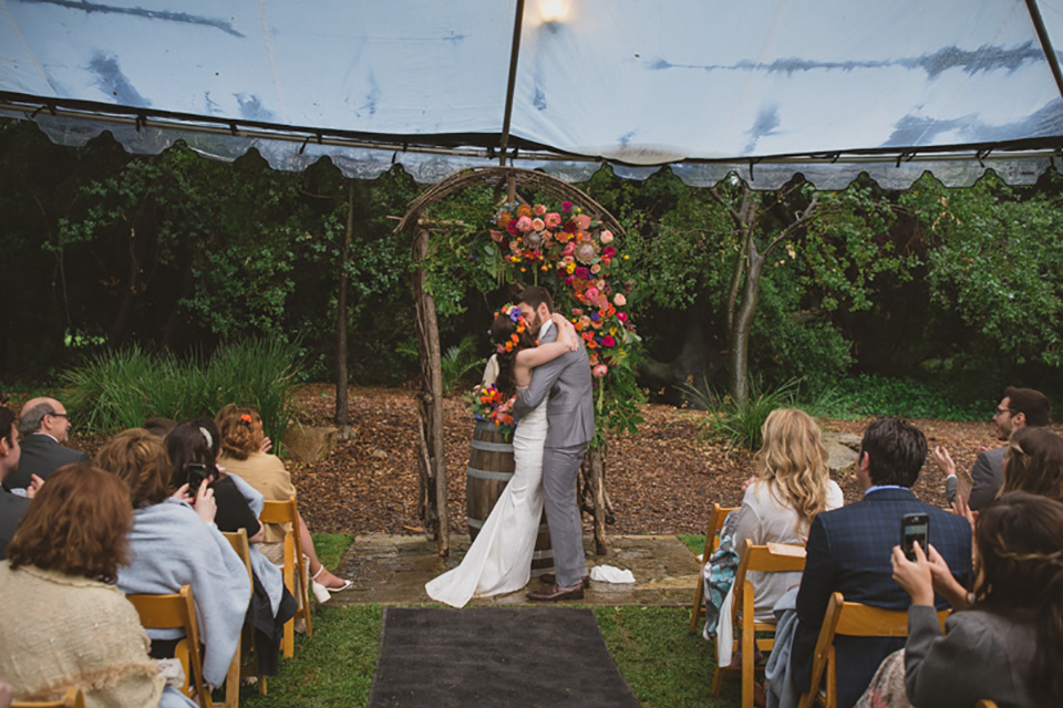 Temecula outdoor wedding at temecula creek inn bride form fitting simple strapless gown with a straight neckline and teal rain boots with groom grey notch lapel suit with a white dress shirt and long brown tie with an orange floral boutonniere kissing during ceremony