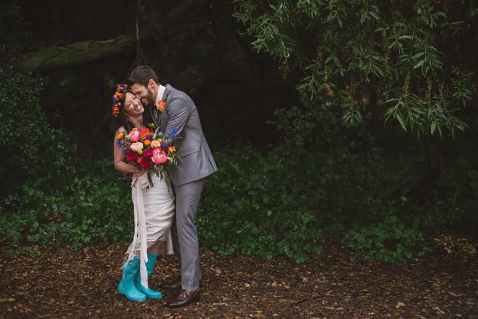 Temecula outdoor wedding at temecula creek inn bride form fitting simple strapless gown with a straight neckline and teal rain boots with groom grey notch lapel suit with a white dress shirt and long brown tie with an orange floral boutonniere hugging and kissing bride holding colorful floral bridal bouquet
